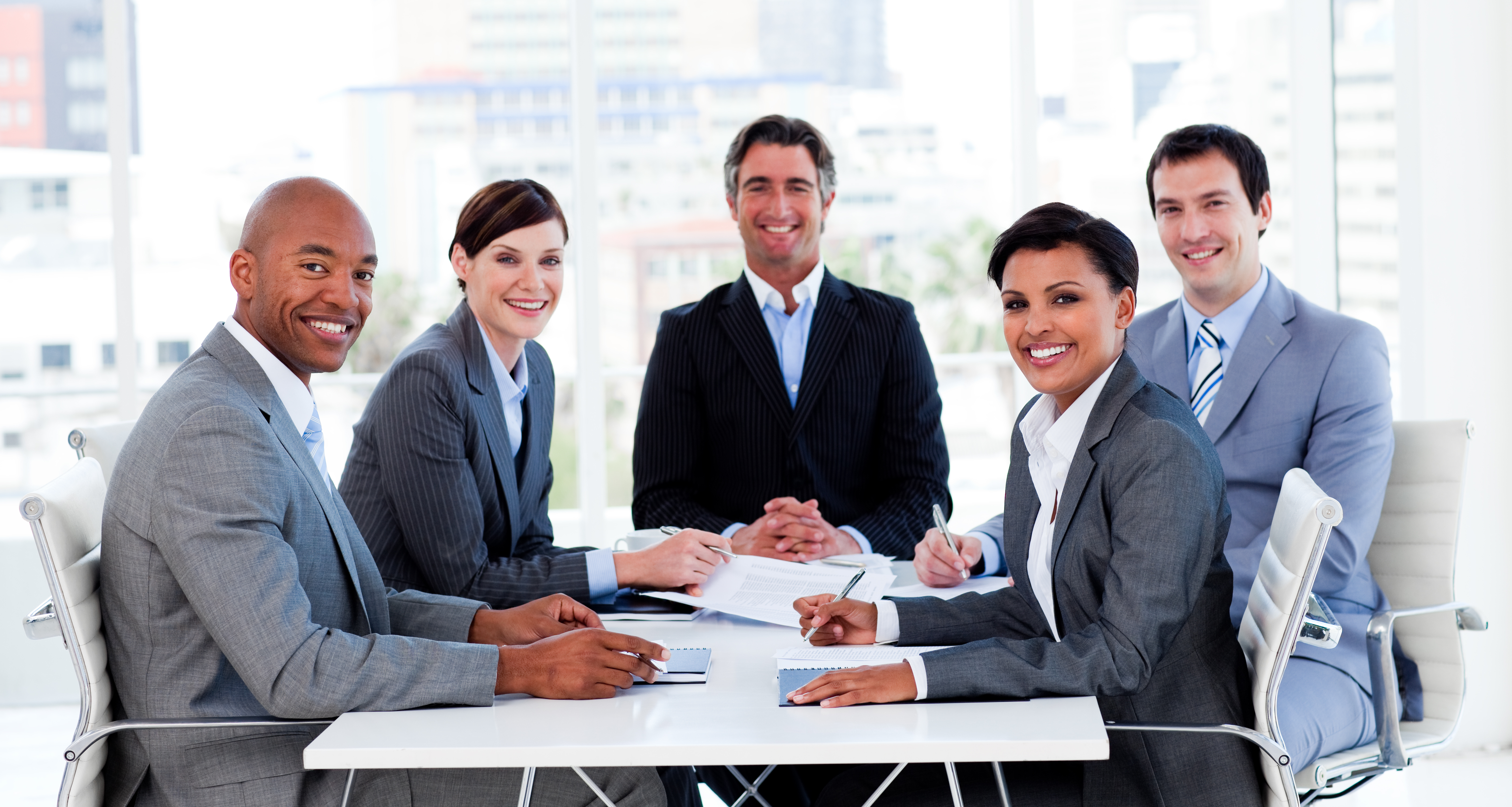 Business group showing ethnic diversity in a meeting smiling at the camera